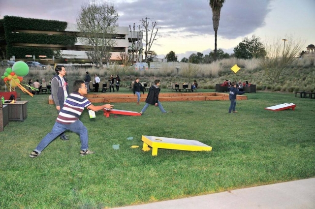 Men play cornhole game outside convention center