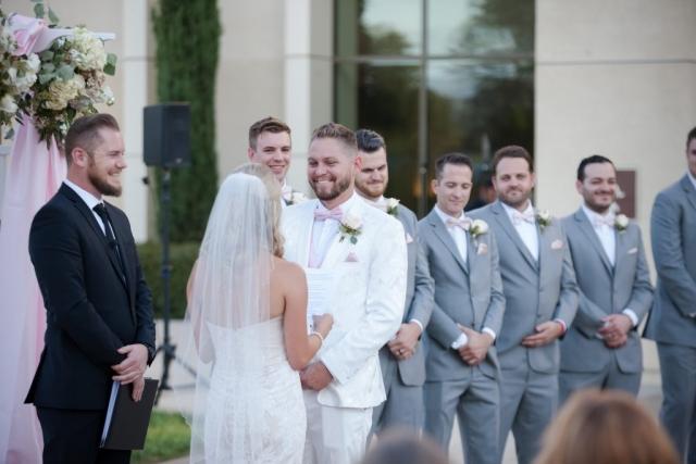 Groom looks happily at bride with groomsmen in back