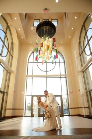Bride and groom pose under chandelier
