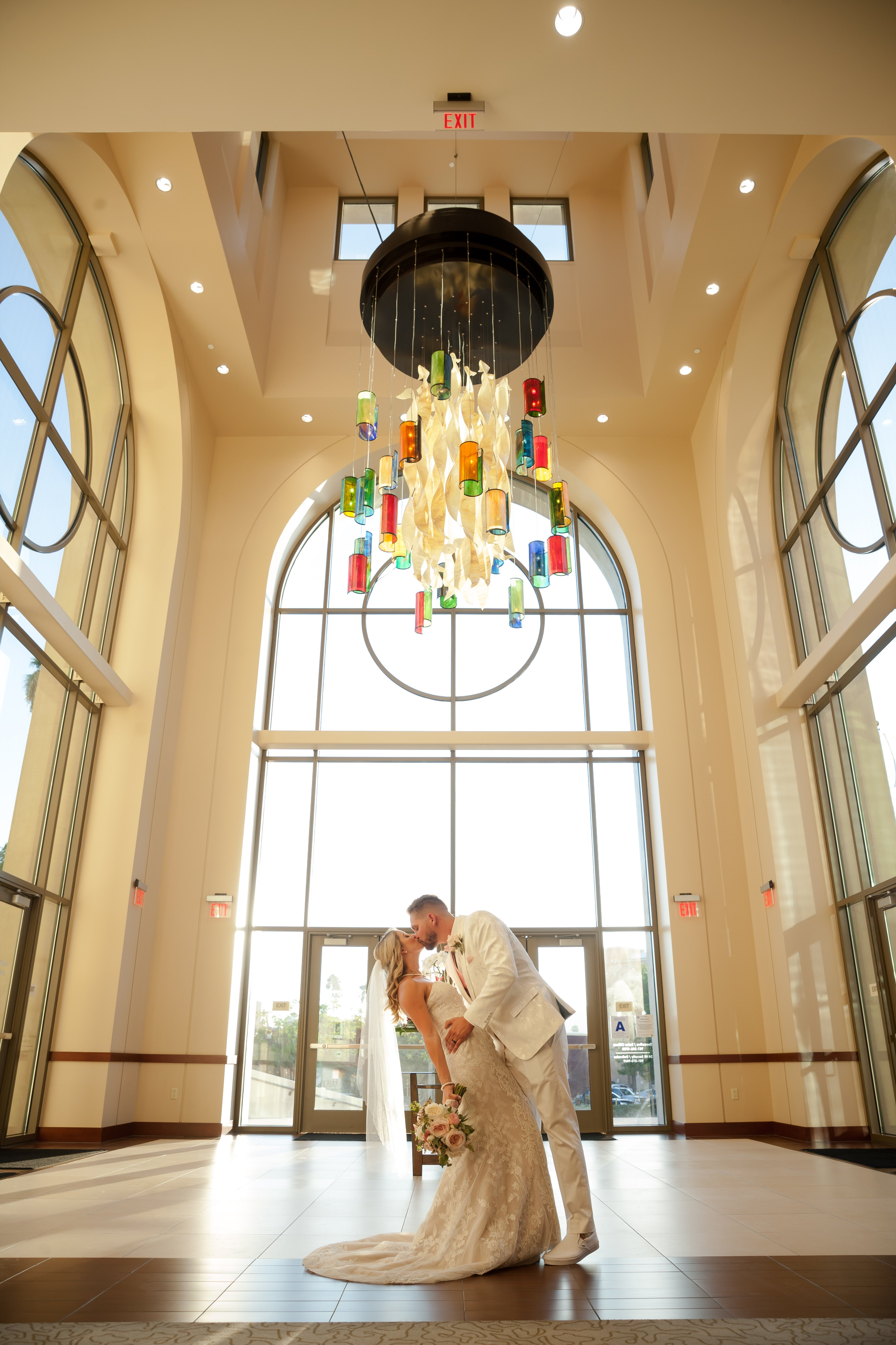 Bride and groom kiss under the convention center's chandelier