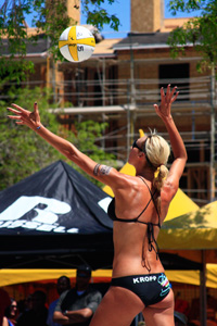 Woman serves volley ball during game
