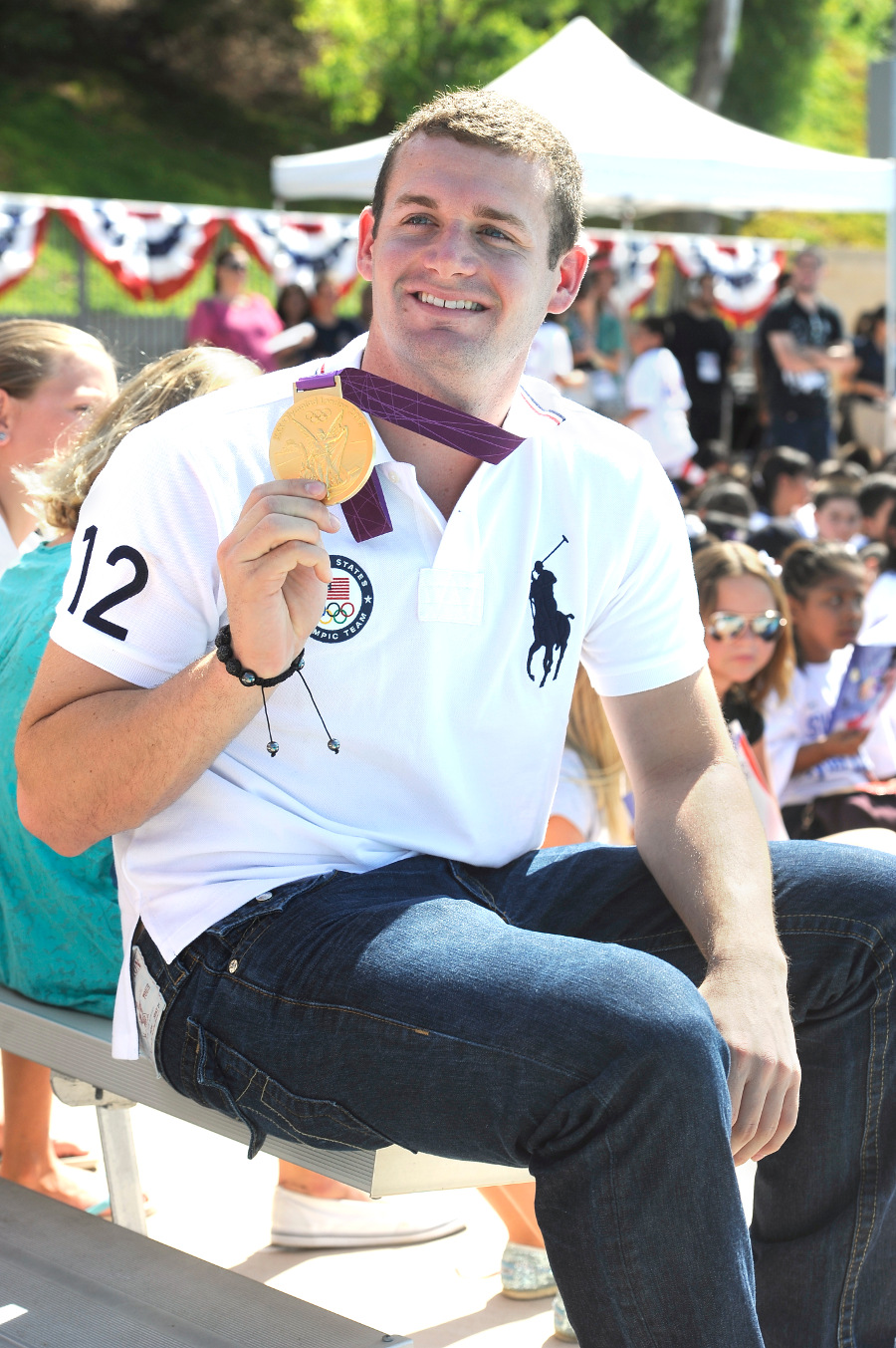Olympic Gold Medalist Tyler Clary London holds up his medal.
