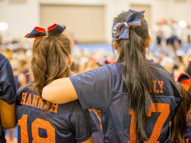 Two cheerleaders watch at cheer camp