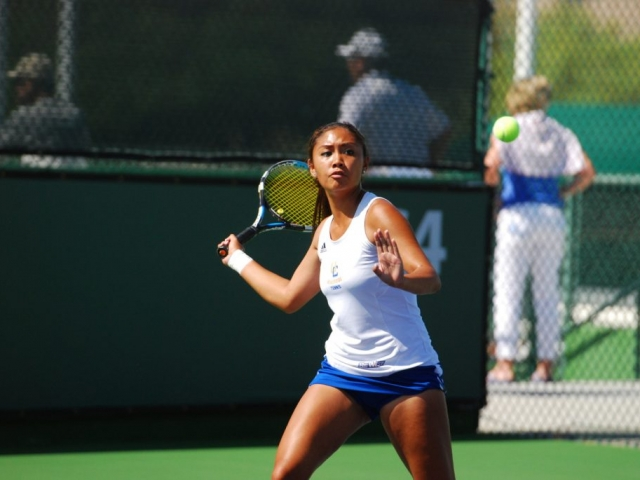 Woman tennis player poises to return volley at UCR.